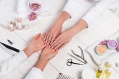 cropped image of manicurist looking at hands of woman at table with flowers, towels, nail polishes, nail files, nail clippers, sea salt, cream, cuticle pusher, scissors and aroma oil bottles