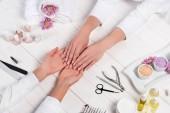 Cropped image de manucure en regardant les mains de femme à table avec des fleurs, des serviettes, des vernis à ongles, limes à ongles, ongles, coupe-ongles, sel de mer, crème, cuticules, ciseaux et bouteilles d'huile de parfum