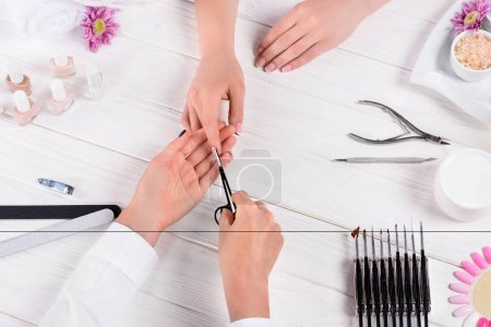Photo for Partial view of beautician doing manicure by scissors to woman at table with nail polishes, nail files, nail clippers, cuticle pusher, cream, sea salt, flowers and samples of nail varnishes - Royalty Free Image