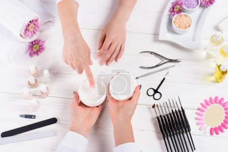 cropped shot of woman pointing on cream in hands of manicurist at table with nail polishes, nail files, nail clippers, cuticle pusher, sea salt, flowers, aroma oil bottles and samples of nail varnishes