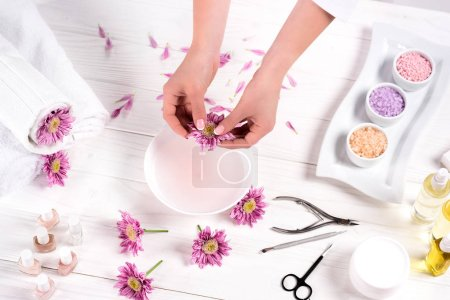 Photo for Partial view of woman throwing petals in bath for nails at table with flowers, towels, colorful sea salt, aroma oil bottles, nail polishes, cream container and tools for manicure in beauty salon - Royalty Free Image