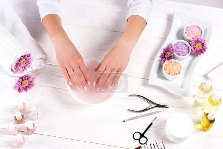 cropped shot of woman receiving bath for nails at table with flowers, towels, colorful sea salt, aroma oil bottles, nail polishes, cream container and tools for manicure in beauty salon