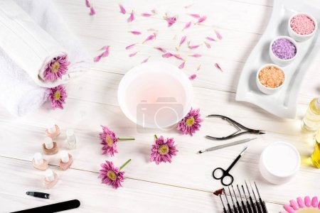 Photo for Elevated view of bath for nails at table with flowers, petals, towels, nail polishes, nail file, cuticle pusher, nail clippers, scissors, sea salt, cream container, aroma oil bottles and nail samples of nail varnishes at table - Royalty Free Image