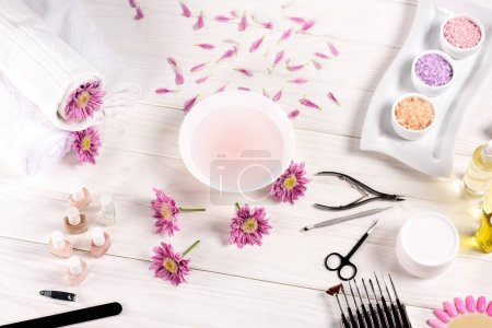 Photo for Top view of bath for nails at table with flowers, petals, towels, nail polishes, nail file, cuticle pusher, nail clippers, scissors, sea salt, cream container, aroma oil bottles and nail samples of nail varnishes for manicure at table - Royalty Free Image