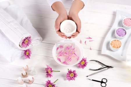 cropped shot of woman holding cream over table with bath for nails, flowers, towels, colorful sea salt, nail polishes and tools for manicure in beauty salon