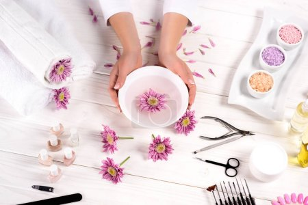 Photo for Partial image of woman holding bath for nails over table with flowers, towels, colorful sea salt, aroma oil bottles, nail polishes, cream container and tools for manicure in beauty salon - Royalty Free Image