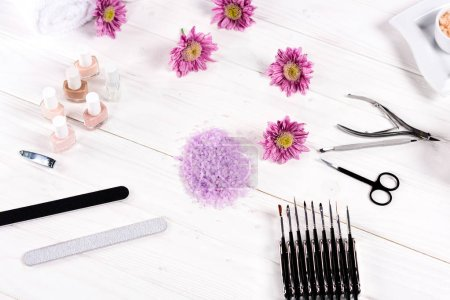 top view of of colorful sea salt, towels, flowers, nail polishes, nail clippers, cuticle pusher, scissors, nail files and instruments for manicure at table in beauty salon