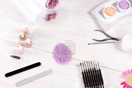 Photo for Elevated view of colorful sea salt, towels, flowers, nail polishes, cream container, nail clippers, cuticle pusher, nail files and samples of nail varnishes for manicure at table in beauty salon - Royalty Free Image