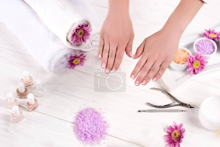 Photo for Partial view of female hands at table with towels, flowers, nail polishes, colorful sea salt, cream container and tools for manicure in beauty salon - Royalty Free Image