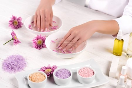 partial view of woman receiving bath for nails at table with flowers, colorful sea salt, cream container, aroma oil bottles and nail polishes in beauty salon