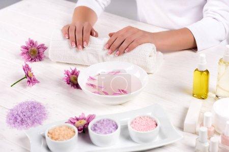 Photo pour Image recadrée de femme tenant par la main sur la serviette pour procédure de manucure à table avec des fleurs, sel de mer coloré, contenant crème, bouteilles d'huile de parfum et vernis à ongles dans un salon de beauté - image libre de droit