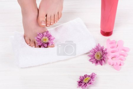 cropped image of barefoot woman on towel near flowers, toe finger separators and cream container in beauty salon