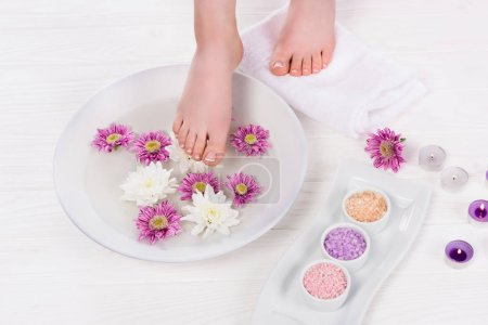 cropped shot of barefoot woman receiving bath for nails with colorful sea salt and flowers near aroma candles in beauty salon