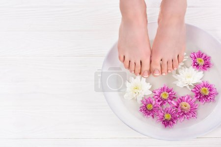 partial view of barefoot woman receiving bath for nails flowers in beauty salon