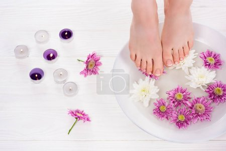 cropped shot of barefoot woman receiving bath for nails flowers near aroma candles in beauty salon