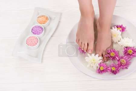 partial view of barefoot woman receiving bath for nails with sea salt and flowers in beauty salon
