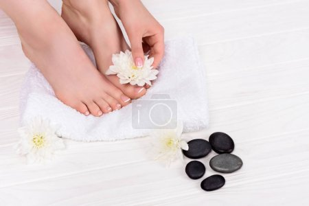 partial view of barefoot woman on spa treatment with towel, flowers and spa stones