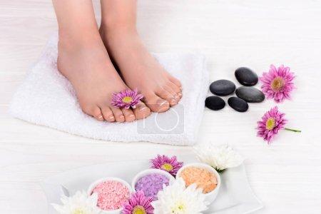 Photo pour Image recadrée de femme pieds nus sur la cure thermale de serviette, des fleurs, des pierres de sel et spa mer colorée - image libre de droit