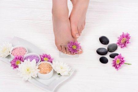 Photo pour Image recadrée de femme pieds nus sur le traitement spa avec des fleurs, du sel de mer coloré et des pierres de spa - image libre de droit