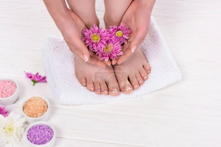 Photo pour Photo recadrée de femme pieds nus tenant des fleurs près du sel de mer coloré dans un salon de beauté - image libre de droit