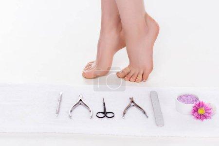 Photo pour Bouchent la vue des outils pour pédicure, sel de mer avec fleur et femme pieds nus sur fond blanc - image libre de droit