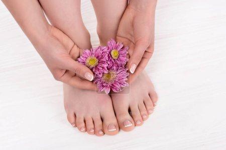 Photo pour Vue partielle d'une femme aux pieds nus avec des fleurs sur la procédure de pédicure en salon de beauté - image libre de droit