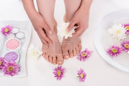 cropped shot of barefoot woman with flowers, candles, colorful sea salt and bath for nails in beauty salon