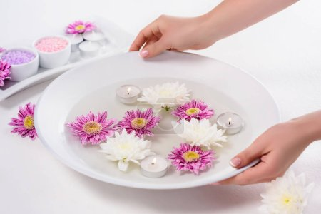 cropped shot of woman holding bath for nails with flowers and aroma candles at table in beauty salon