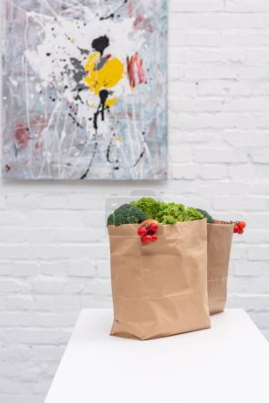 grocery store bags with vegetables on table in front of white brick wall with abstract picture