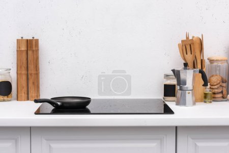 Photo for Frying pan on induction panel at modern kitchen in front of blank white wall - Royalty Free Image