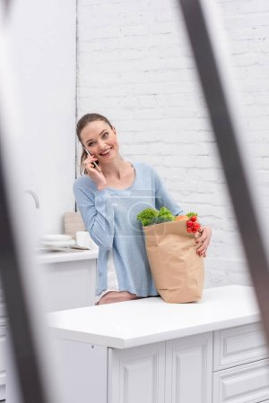 smiling adult woman with paper bag talking by phone at kitchen