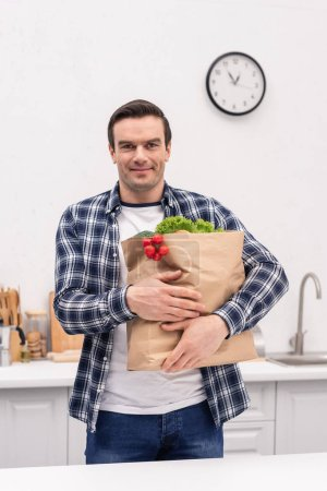 smiling adult man carrying grocery store bag at kitchen and looking at camera