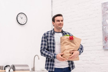 smiling adult man carrying grocery store bag at kitchen