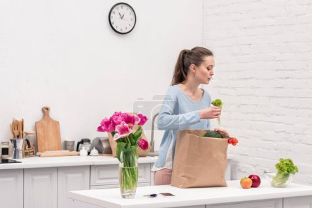 Photo for Beautiful adult woman taking fruits and vegetables out of paper bag at kitchen - Royalty Free Image