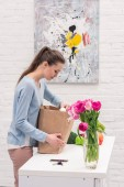 beautiful smiling adult woman taking fruits and vegetables out of paper bag