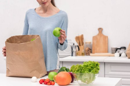 cropped shot of smiling adult woman taking fruits and vegetables out of paper bag