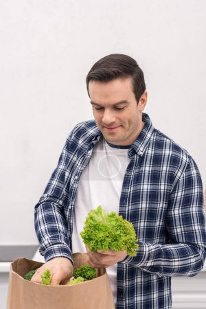 smiling adult man unpacking grocery store paper bag at kitchen