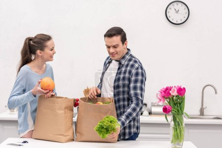 Photo for Beautiful adult couple taking vegetables and fruits out of paper bags from grocery store - Royalty Free Image