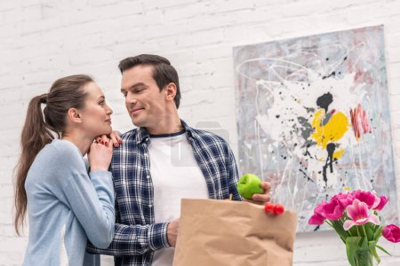 adult man looking at his beautiful wife while unpacking bag from grocery store