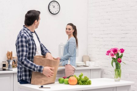 adult man chatting with wife while unpacking bag from grocery store