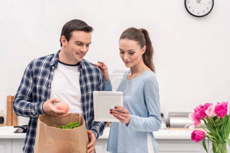 attractive adult couple checking buys list in tablet after grocery shopping