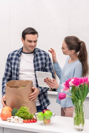 happy adult couple checking buys list in tablet after grocery shopping
