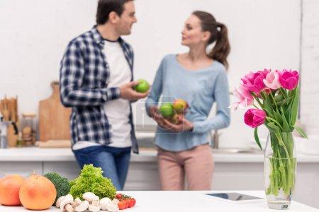 gesundes Essen liegt auf dem Tisch in der Küche mit einem Blumenkasten, während schönes erwachsenes Paar unscharf auf dem Hintergrund plaudert