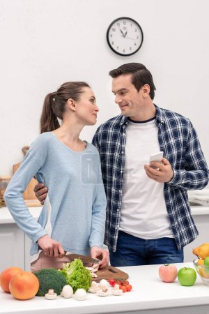 Photo for Happy adult man with smartphone embracing his wife while she preparing dinner - Royalty Free Image