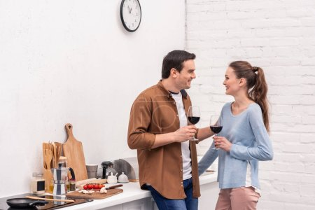 beautiful adult couple with glasses of wine spending time together at kitchen