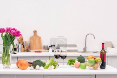 Photo for Various vegetables with red wine and flowers on table at kitchen - Royalty Free Image