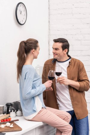 beautiful adult couple clinking glasses of champagne on kitchen