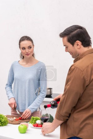 handsome adult man pouring wine in glass for wife while she cooking