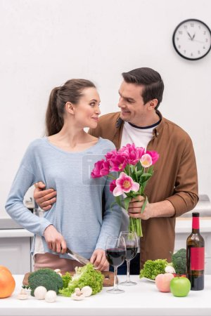 handsome adult man presenting tulips bouquet for wife while she cooking