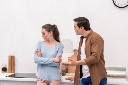 mad adult man looking at wife while she ignoring him after argument at kitchen